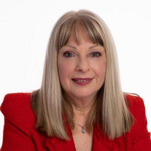 Headshot of female wearing red jacket on white background