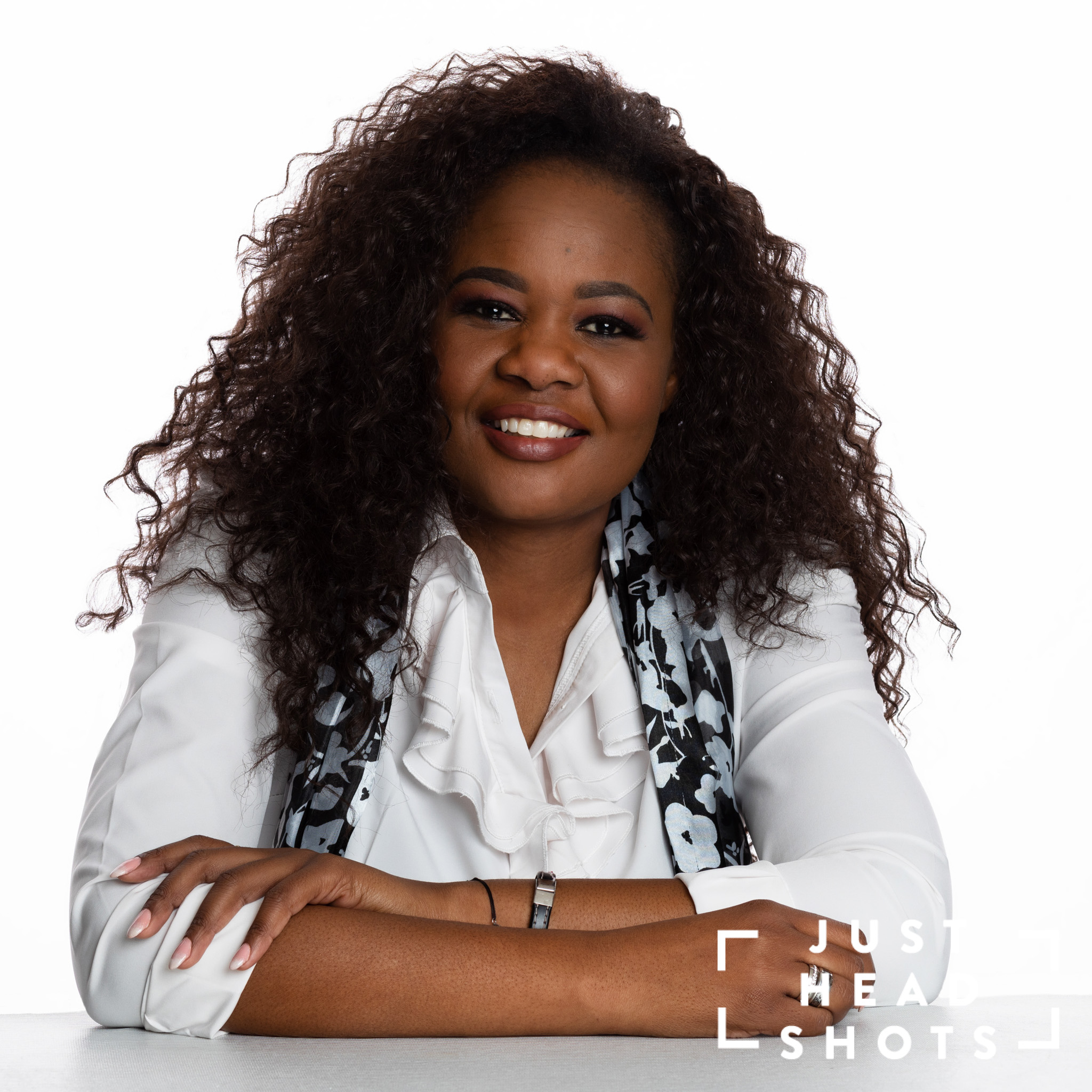 Professional headshot of a black woman wearing a white blouse and scarf, photographed with Profoto studio flash on white background with shoulders angled directly to the camera with arms folded and leaning on a table.
