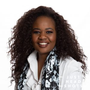 Professional headshot of a black woman wearing a white blouse and scarf, photographed with Profoto studio flash on white background with shoulders angled to the left of the photo.