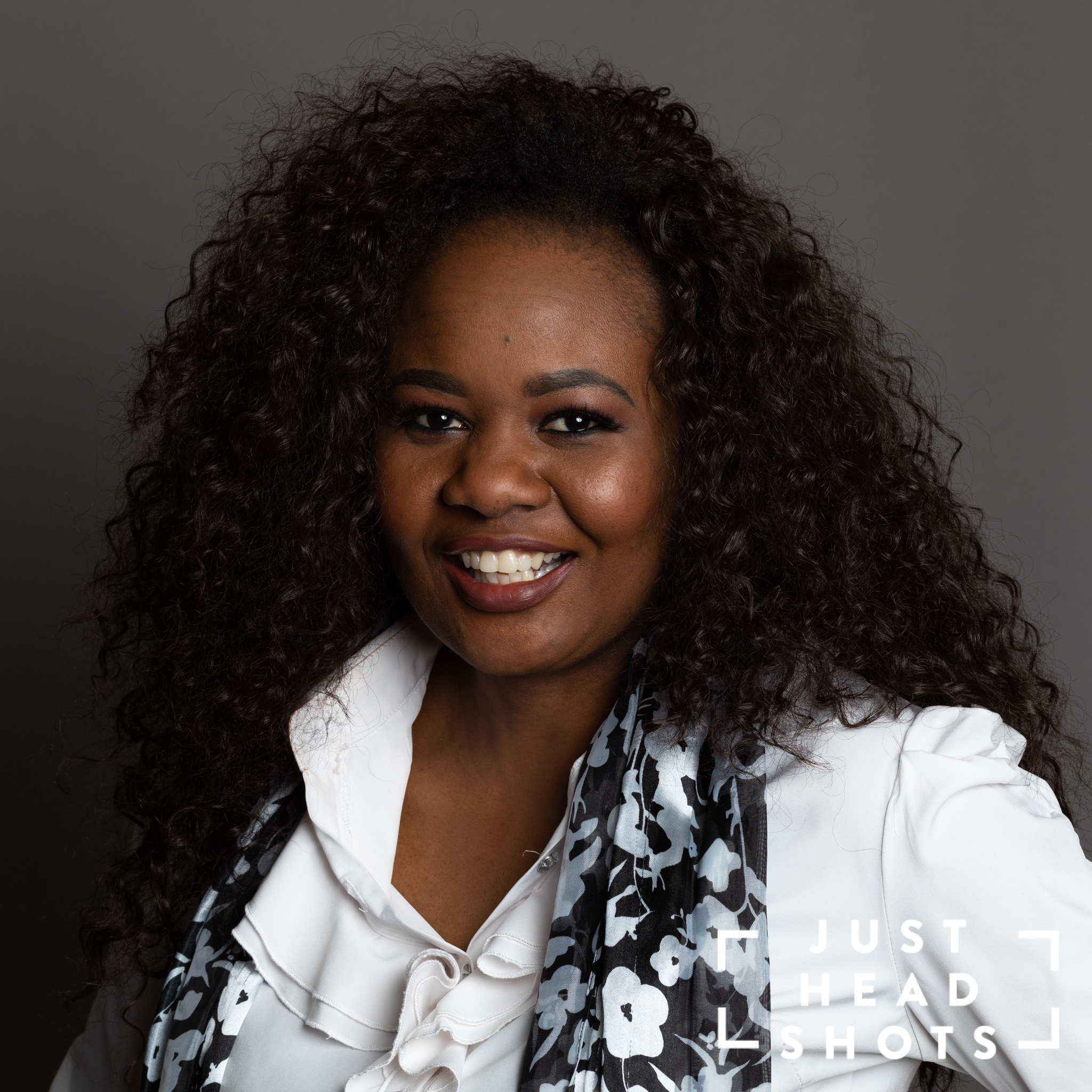 Professional headshot of a black woman wearing a white blouse and scarf, photographed with Profoto studio flash on dark grey background with shoulders angled to the left of the photo.