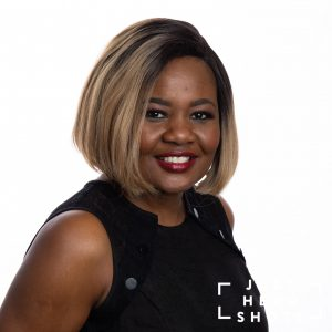Professional headshot of a black woman wearing a black sleeveless blouse, photographed with Profoto studio flash on white background with shoulders angled to the right of the photo.