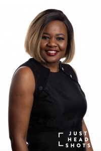Professional close cropped headshot of a black woman wearing a black sleeveless blouse, photographed with Profoto studio flash on white background with shoulders angled to the right of the photo.