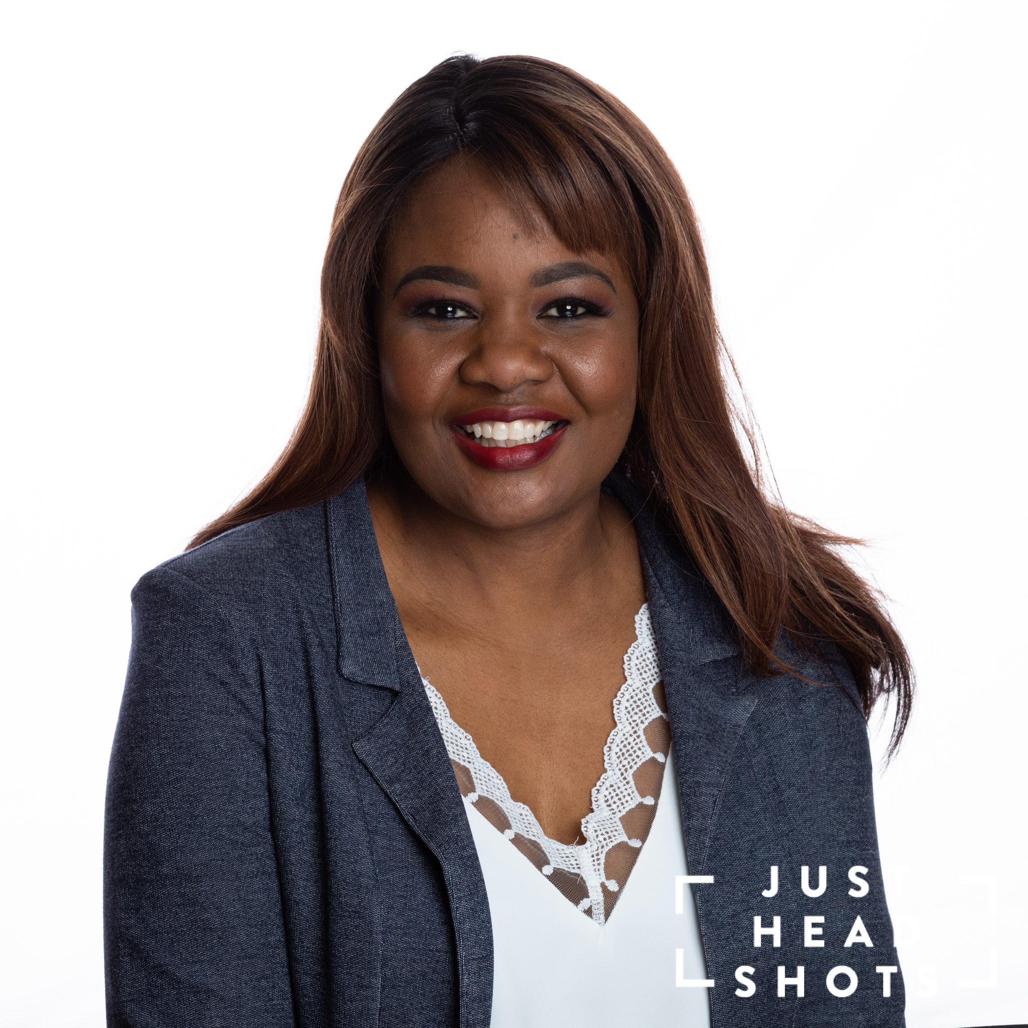 Professional headshot of a black woman wearing a white blouse and grey jacket photographed with Profoto studio flash on white background with shoulders angled to the right of the photo.