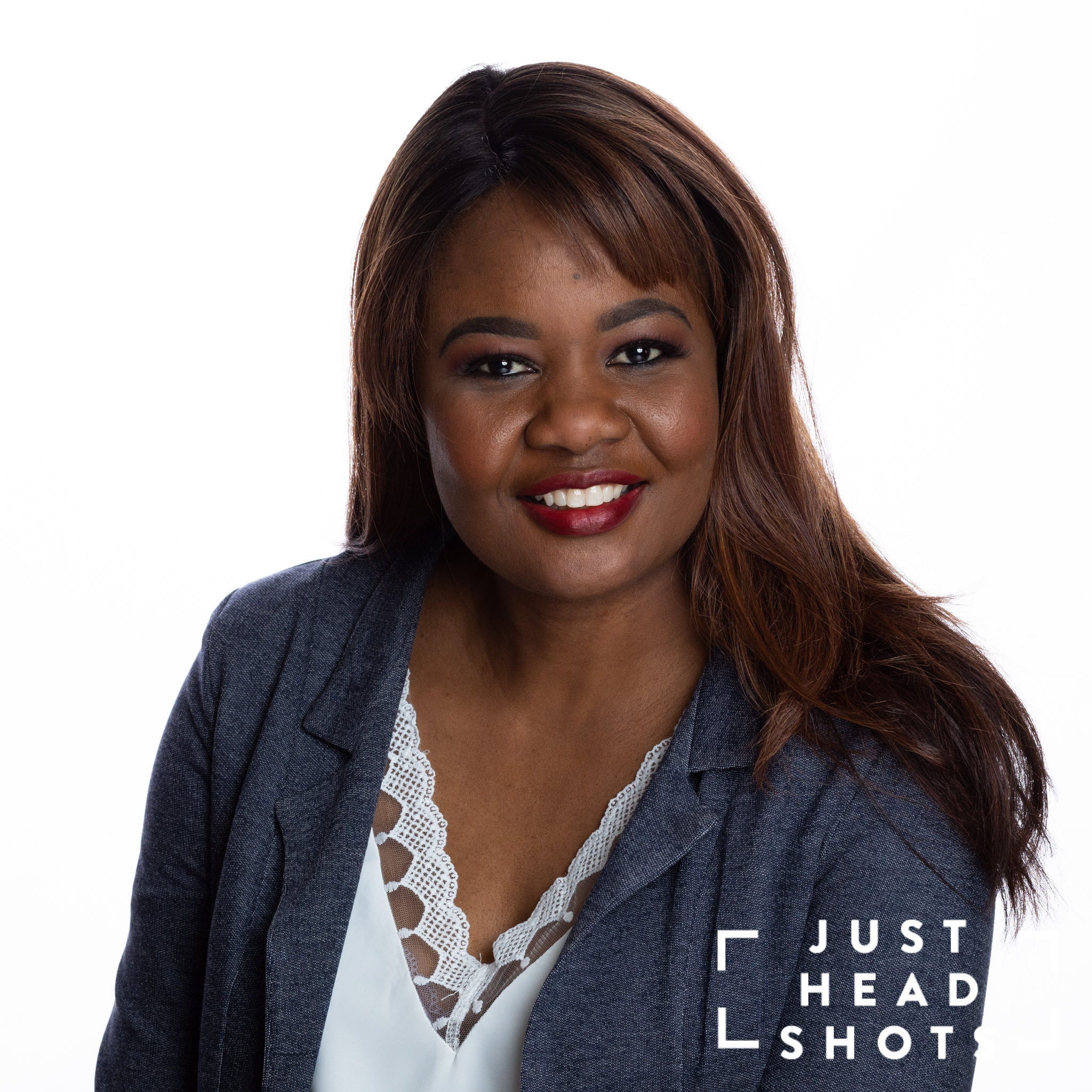 Professional headshot of a black woman wearing a white blouse and grey jacket photographed with Profoto studio flash on white background with shoulders angled to the left of the photo.