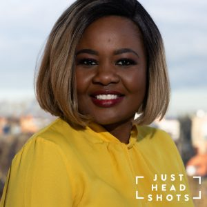 Professional headshot of a black woman wearing a yellow blouse photographed with flash and natural light with Chester city centre in the background.