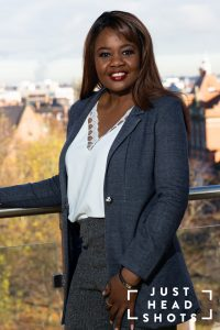 Three-quarter body business portrait of a black woman photographed in a portrait format as a PR photo, with flash and natural light with Chester city centre in the background.