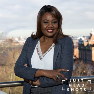 Head and shoulders business portrait of a black woman wearing a white blouse and grey jacket photographed with flash and natural light with Chester city centre in the background.