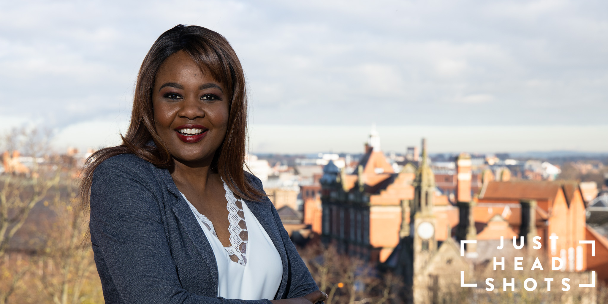 Upper body business portrait of a black woman photographed in a wide format as a banner for website, with flash and natural light with Chester city centre in the background.
