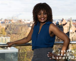 Upper body business portrait of a black woman photographed with flash and natural light with Chester city centre in the background.
