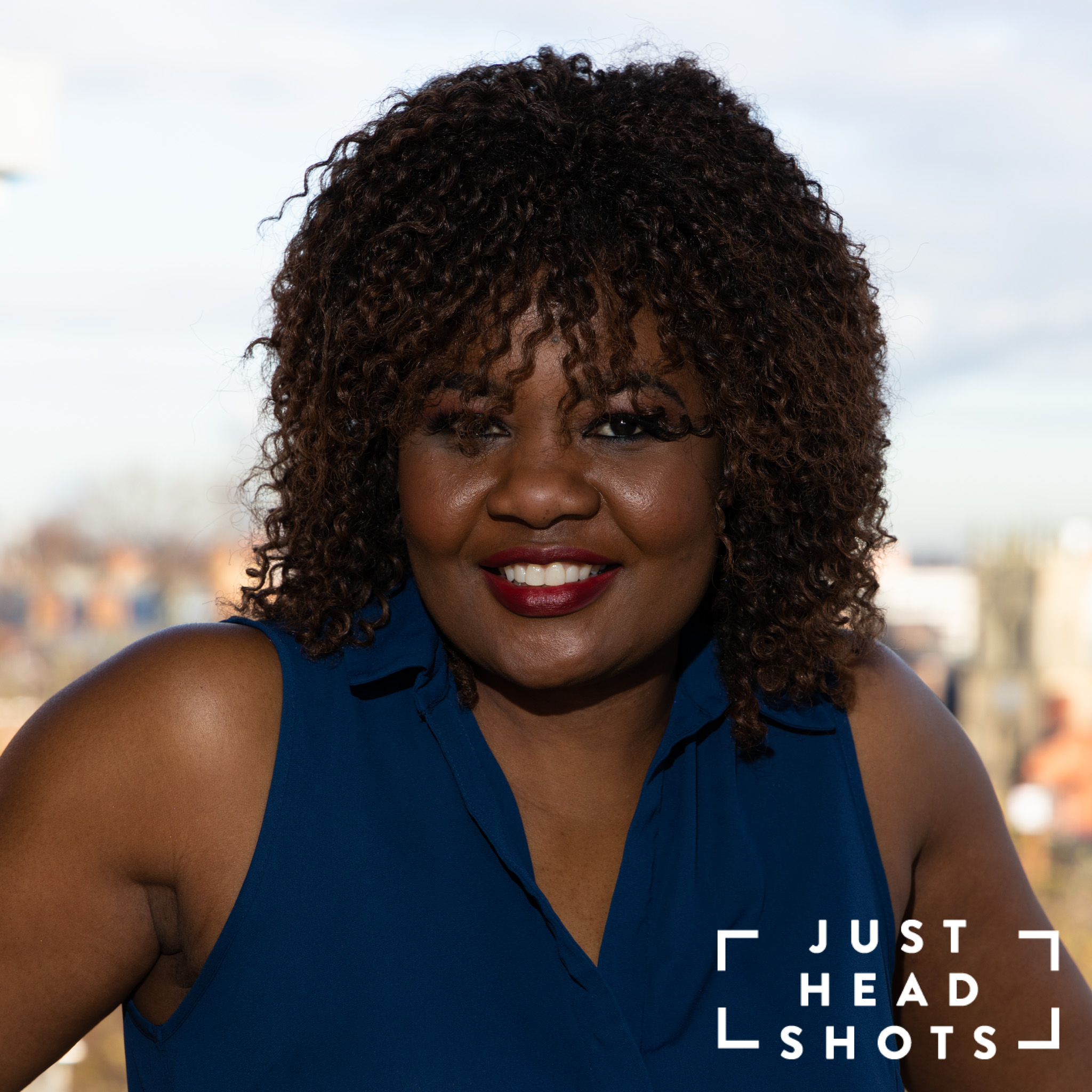 Head and shoulders business portrait of a black woman wearing a blue sleeveless blouse photographed with flash and natural light with Chester city centre in the background.