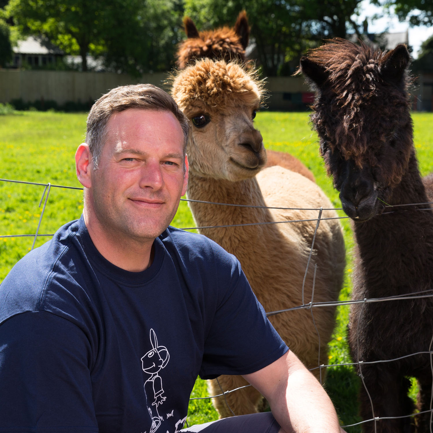 Headshot of charity worker with alpacas in the background