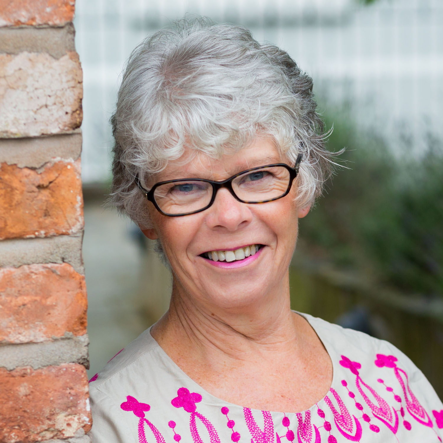 Natural background headshot of Arbonne consultant leaning on brick wall in Cheshire