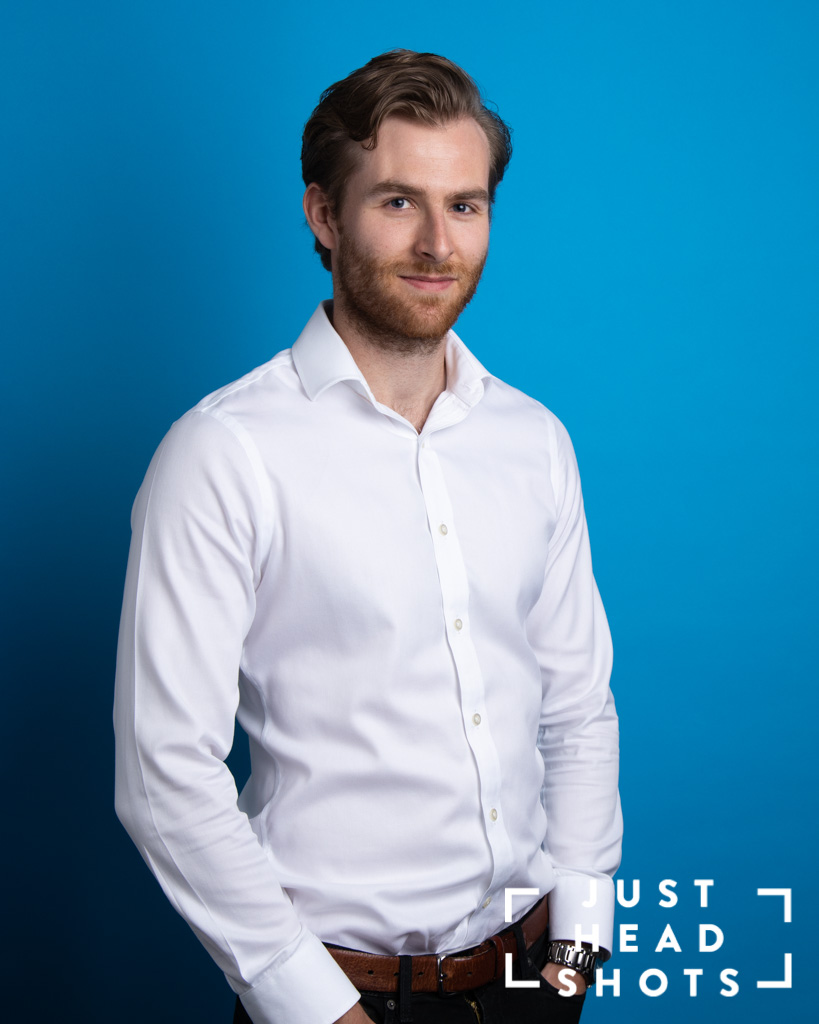 Blue background corporate portrait of man with beard wearing white shirt with shoulders facing left