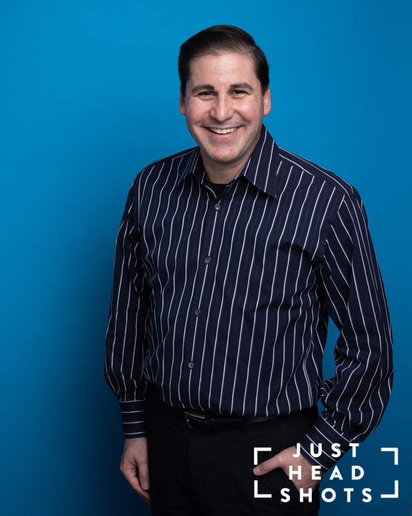 Blue background corporate portrait of man wearing dark striped shirt with shoulders facing Blue background corporate portrait of man with beard wearing dark grey shirt with shoulders facing left