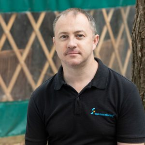 Outdoor headshot of man wearing dark polo shirt with yurt in the background