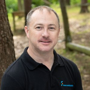 Outdoor headshot of man in Chester wearing dark polo shirt with woodland in the background