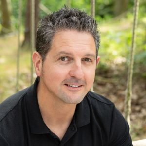 Ambient light headshot of man wearing dark polo shirt with ropes course in the background