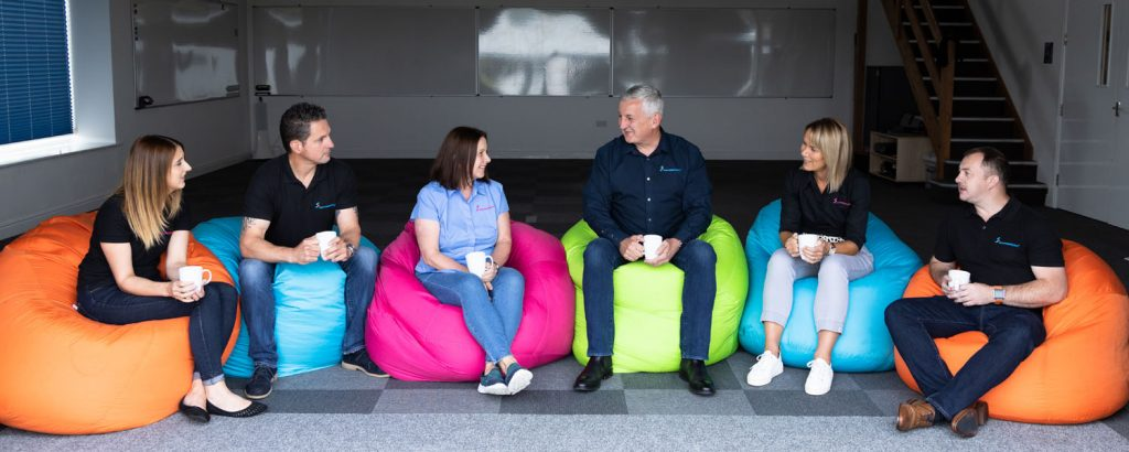 group photo of team sat on bean bags in the training room with cups of coffee