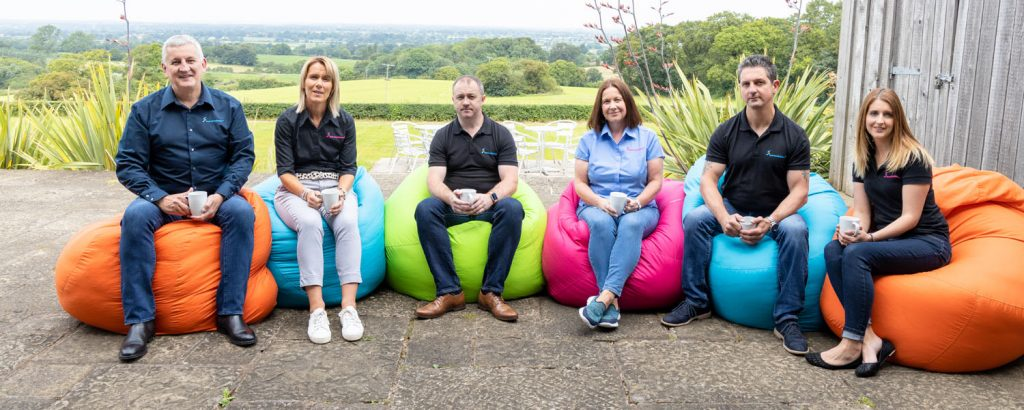group photo of team sat on bean bags on the terrace with cups of coffee