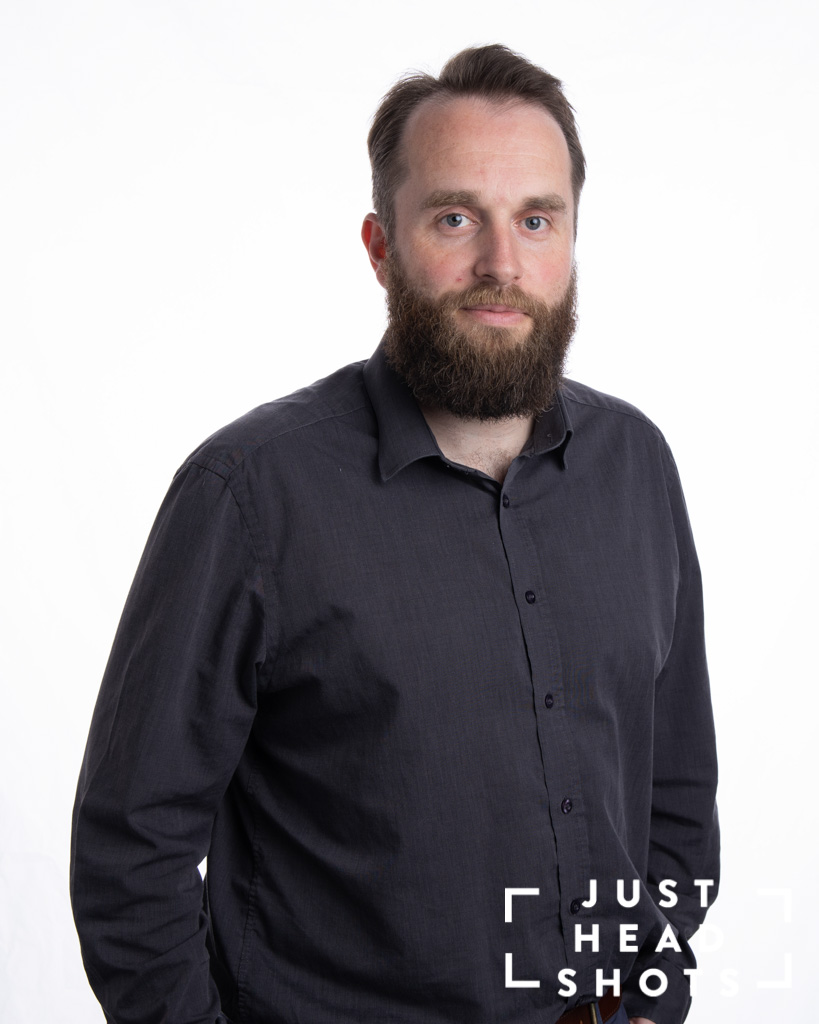 White background corporate portrait of man with beard wearing dark grey shirt with shoulders facing right