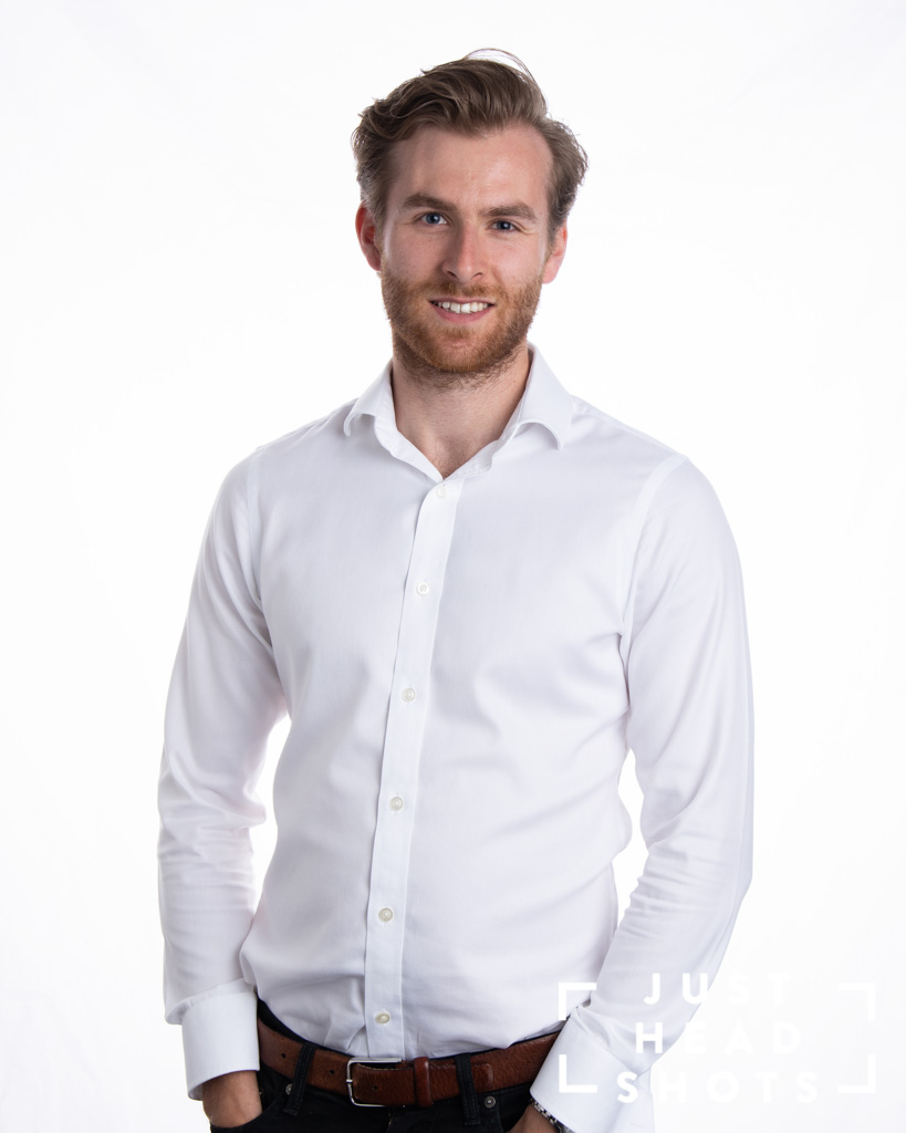 White background corporate portrait of man with beard wearing white shirt with shoulders facing left