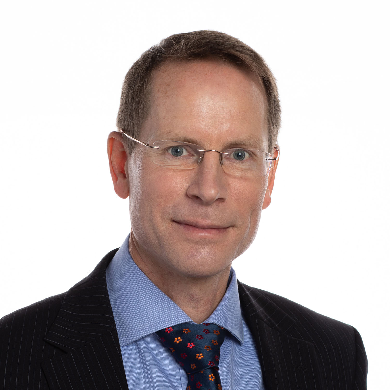 White background headshot of man wearing glasses